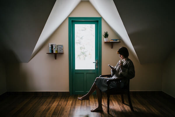 A female part time freelance writer sits in an attic looking at her phone