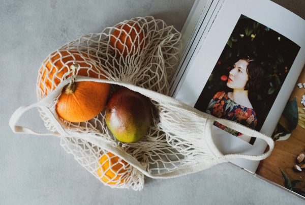 opened cookbook on table together with fruits
